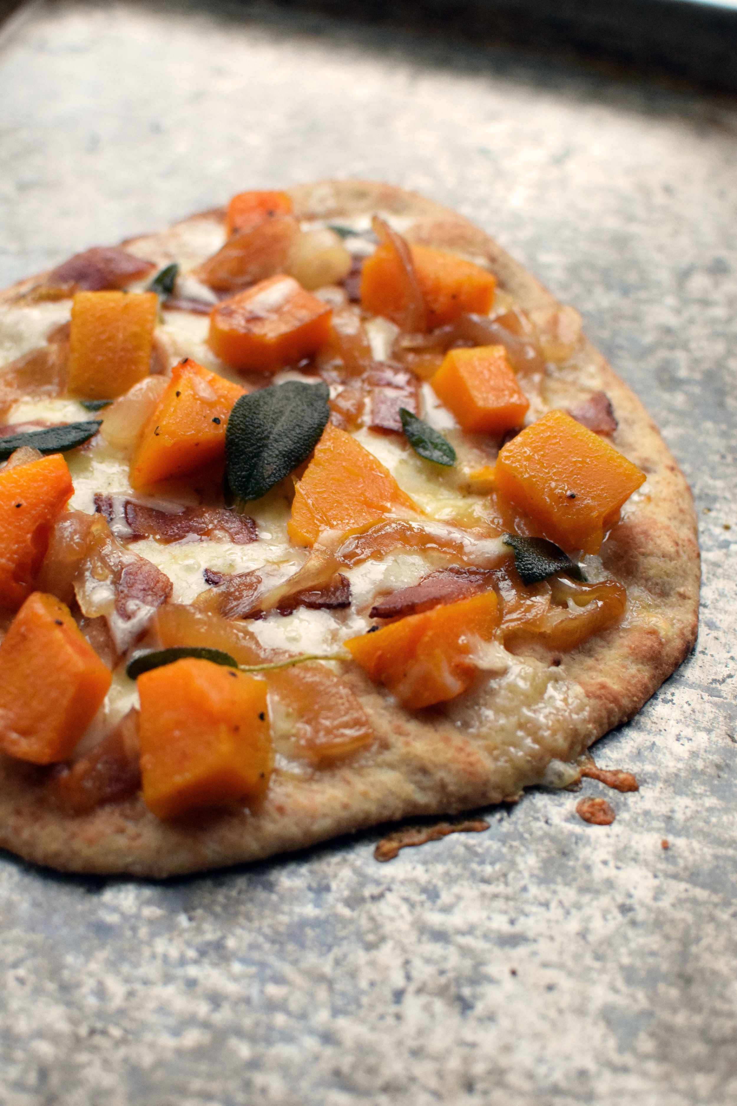 Onions Caramelized in Apple Cider complete this easy, autumn-themed pizza with butternut Squash, sage, and bacon. } themillennialmenu.com