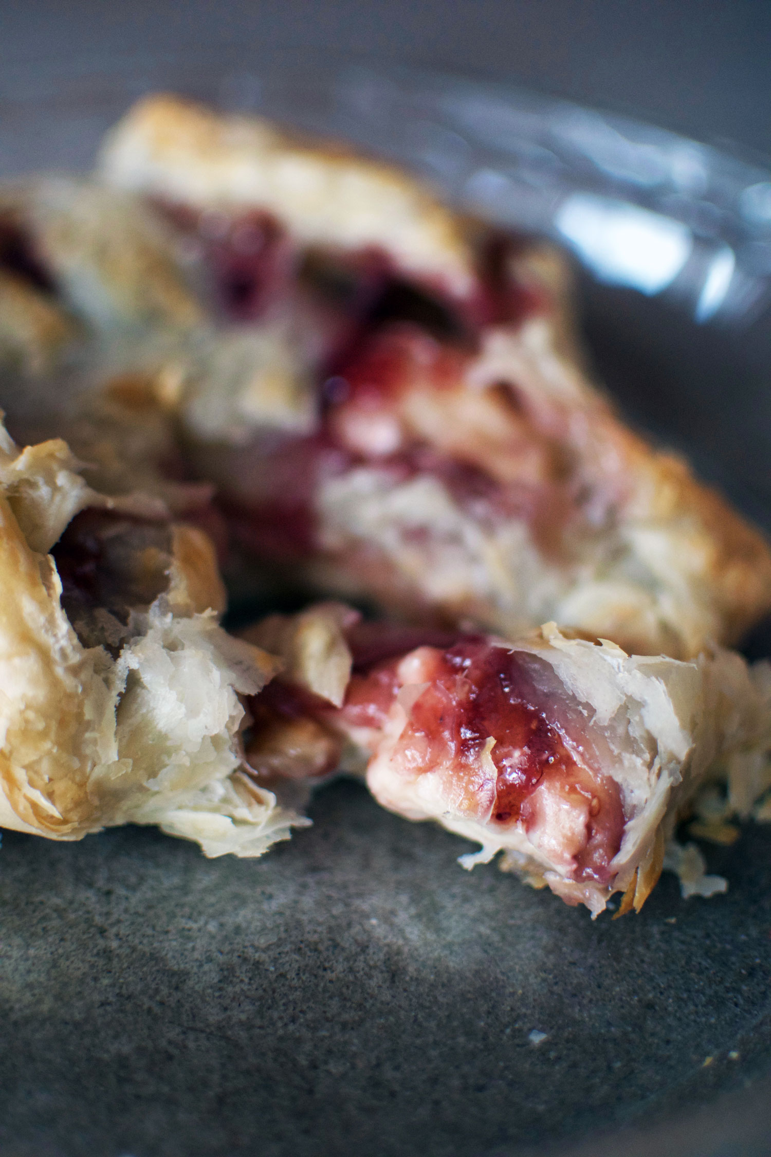 A slice of phyllo-wrapped baked brie oozing with raspberry jam is the easiest appetizer you'll ever make - only 3 ingredients! | themillennialmenu.com