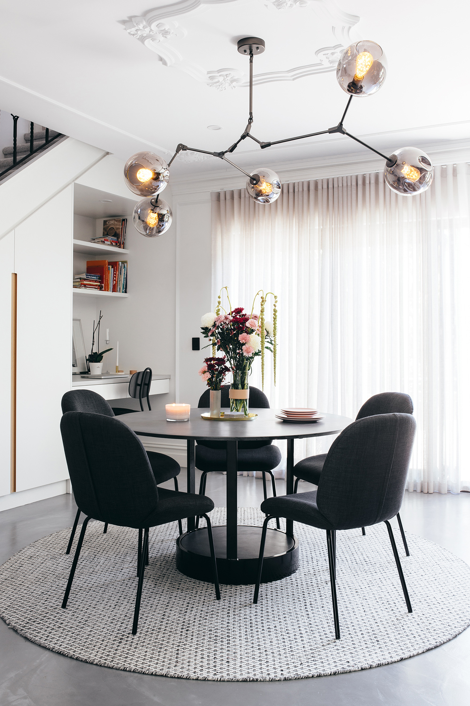 """""""It was a lot of work to add all the wainscoting, ceiling roses and plaster glass cornice throughout our home, but it produced a great result. To achieve a French-feeling interior, those kinds of details are required,"""" says Matt. Replica Lindsey Adelman 'Bubble' chandelier from Lucretia Lighting; 'Bella' dining chairs from GlobeWest; 'Mila' dining table from Nood Co."""