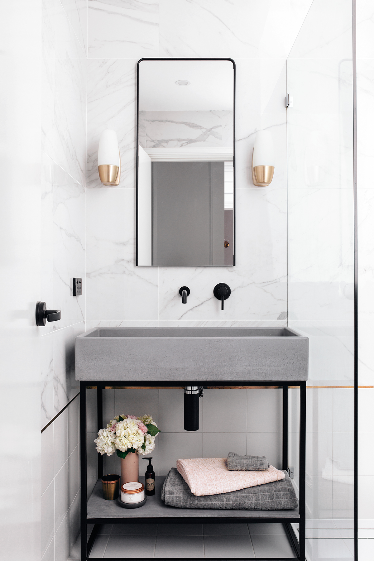 Nood Co.'s trough sink vanity set and 'Zia' mirror, along with the Phoenix matte black tapware, bring a contemporary edge to this elegant space. Wall sconces were a lucky scrapyard find, costing only $5 each.