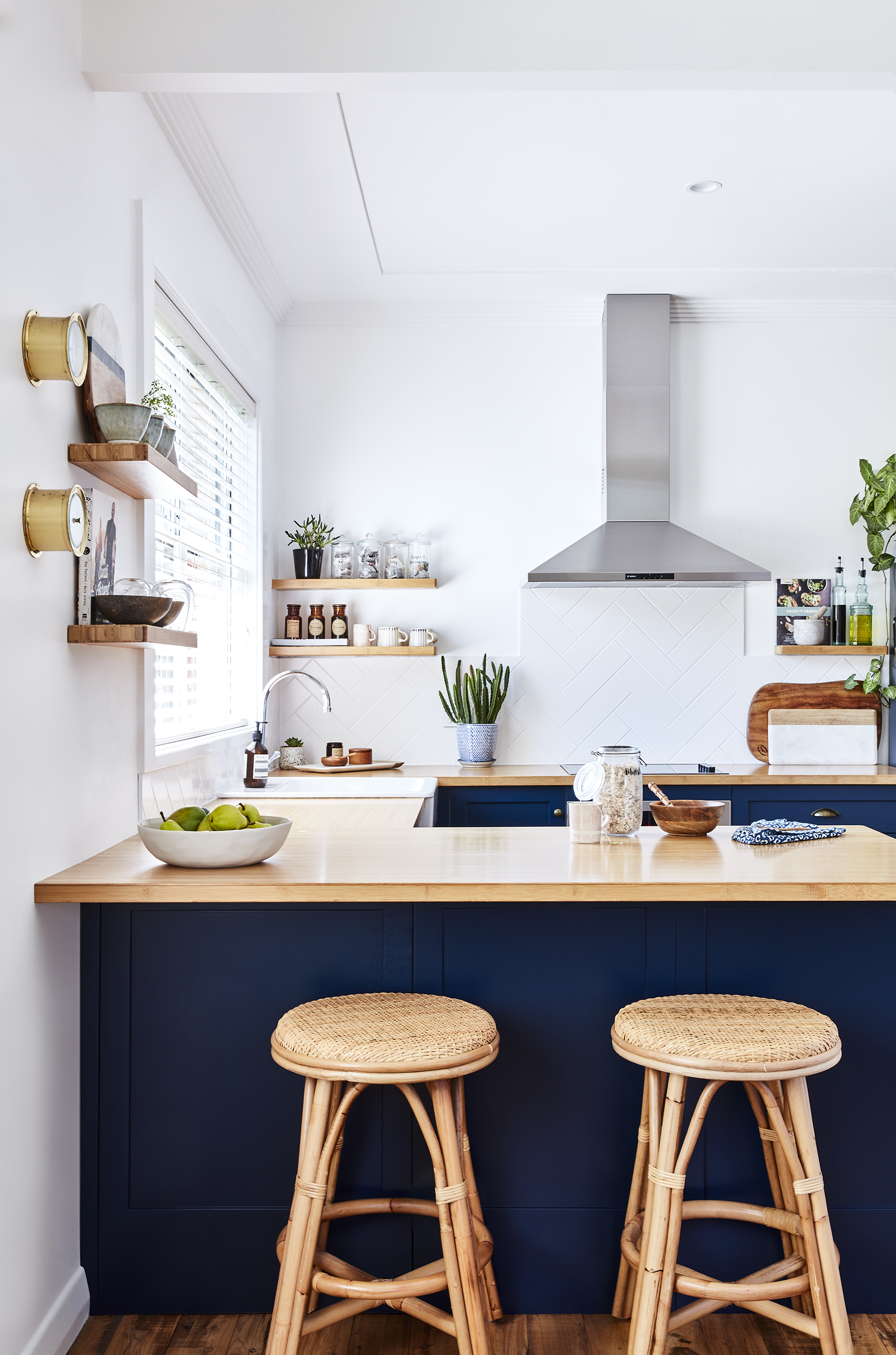 """KITCHEN - """"One of the things we love most about our kitchen and dining, is the natural light. I adore the contrast of our dark cabinets against the wood and white walls,"""" says Maddy. Statement features in this kitchen include bar stools from Naturally Cane and cabinets painted in Taubmans 'Black Granite'."""