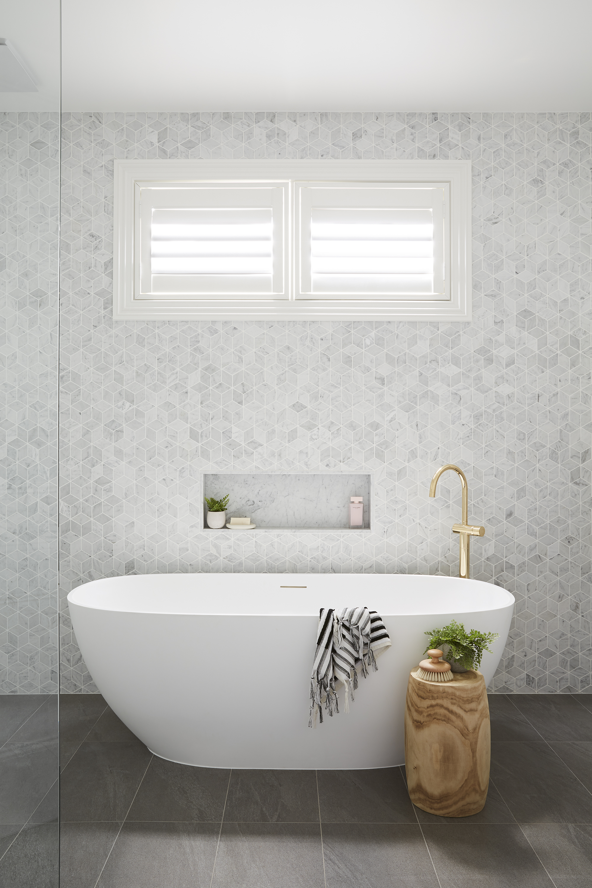 """""""These finishes are quite classic but we modernised them – for example, we've used marble tiles in more contemporary shapes,"""" says Julia.  Tiles from Beaumont Tiles; plantation shutters from DIY Blinds; vanity, Sussex tapware and bath from Reece; towels from Loom Towels."""