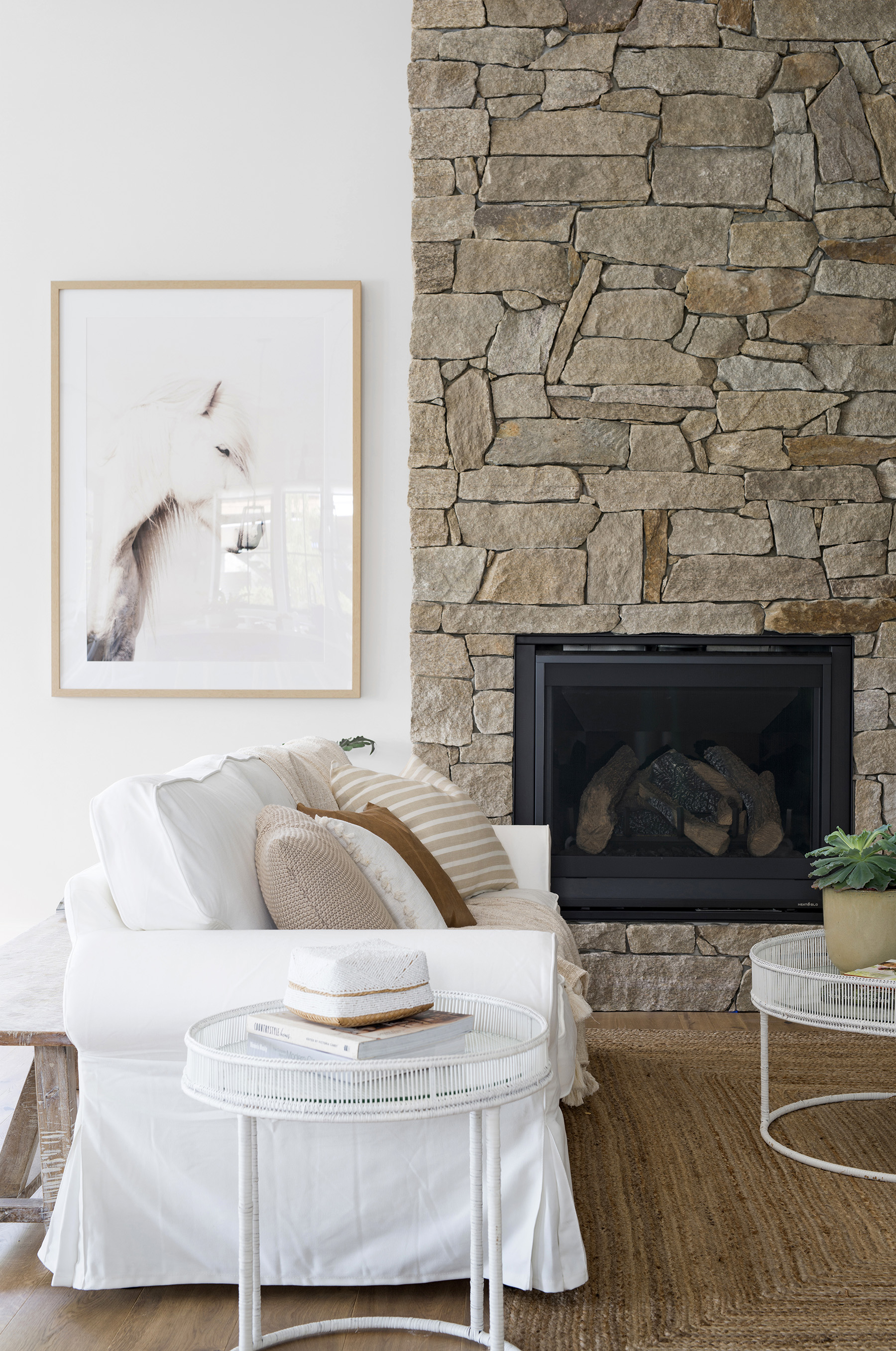 The stone veneer from Infiniti Stone (on the fireplace) creates an authentic farmhouse-style space. Horse print from Urban Road.