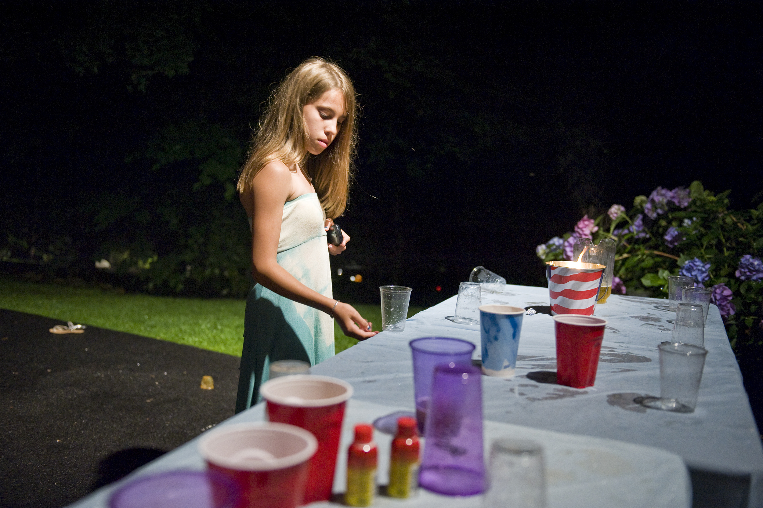 A 13-year-old girl mimics the drinking game played by adults at a engagement party. Chester, New Jersey, 2011.