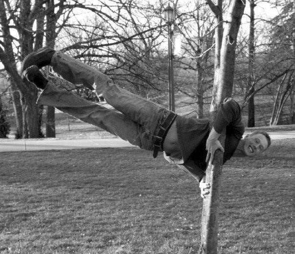Brian demonstrating a flagpole on a tree, probably made easier due to his gymnastics background.