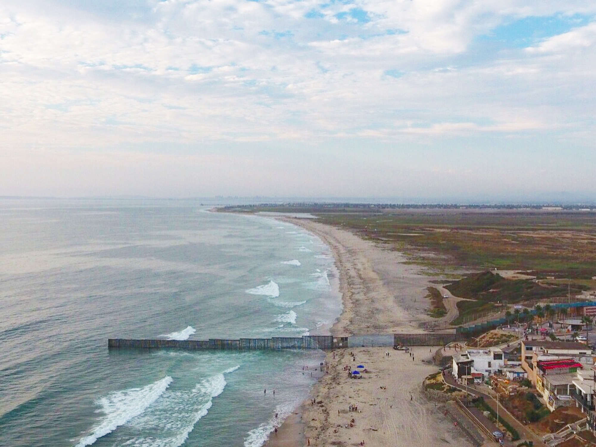Drone shot of the fence from Playas de Tijuana, credit Matt Spencer/Jackie Bryant
