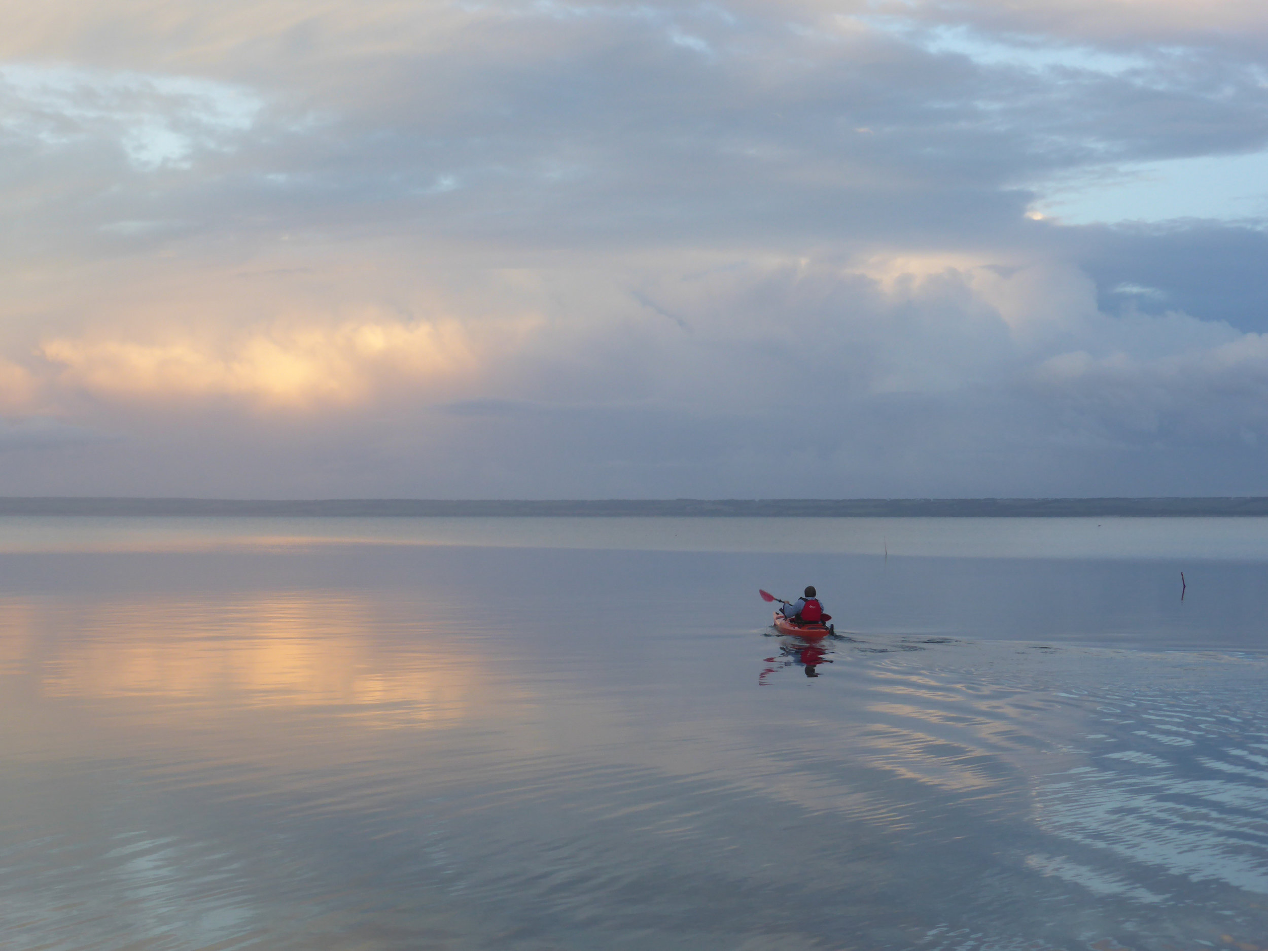 A kayak takes to the sea close to Island Chalet on a calm winter evening