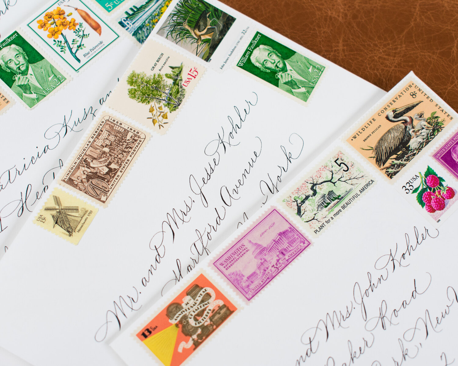Spencerian/Classic script envelope addressing with vintage stamps for wedding invitations.