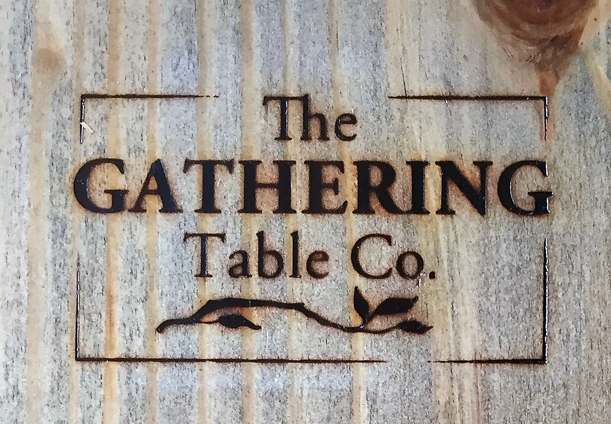 The Gathering Table logo placed on each table by hand with a branding iron