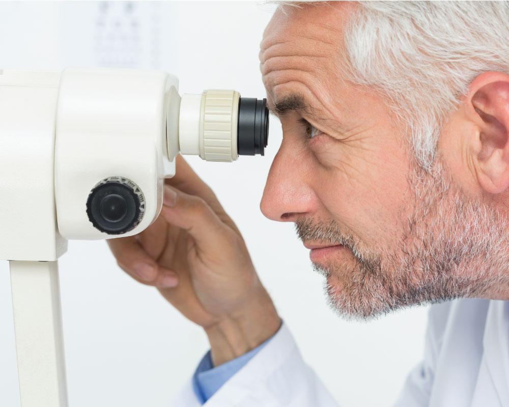 Opthamologist looking through instrument