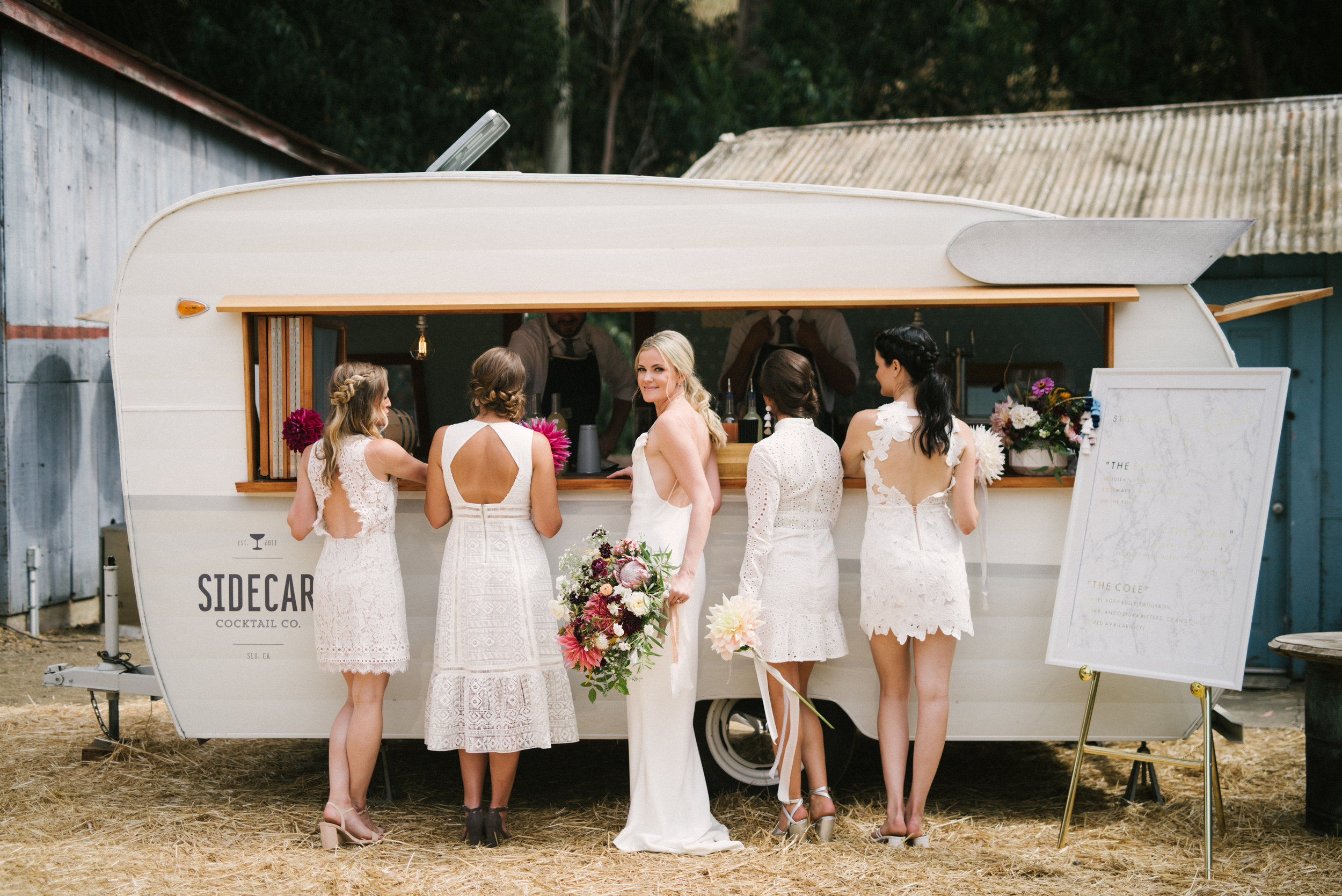 The cutest shot of a bride and her bridesmaids in front of our Sidecar Shasta vintage mobile bar + vending trailer