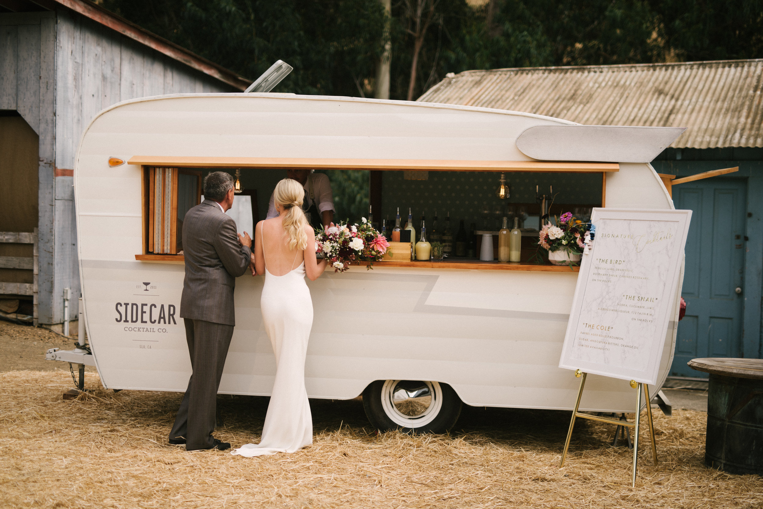 A quiet moment between a bride and her father in front of our Sidecar Shasta Mobile bar and vintage vending trailer.