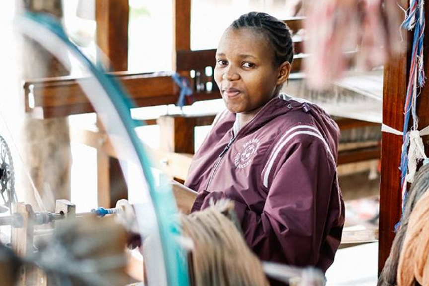 Upendo was born deaf, but this never held her back. The only girl among four siblings, Upendo grew up in the green and fertile Kilimanjaro mountains of Tanzania.  Upendo received limited education as a child, but as a young adult undertook a vocational weaving program. Proactive and determined, Upendo applied to Shanga and joined the weaving team at 23 years old. It was a decision that impacted not just her professional life, but also her personal life.  Upendo and her now-husband, Livingstone, met at Shanga. During lunch breaks and leisurely walks home Upendo and Livingstone, who is also deaf, fell in love. The couple married in 2015 and now their Shanga employment supports their healthy baby girl.