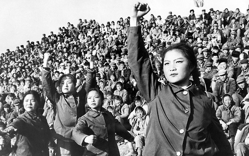 Young female workers perform an anti-Confucian Maoist ballet for a crowd of onlookers.