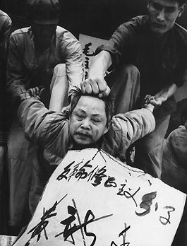 Red Guards punish a man perceived as being in opposition to Maoist ideology.