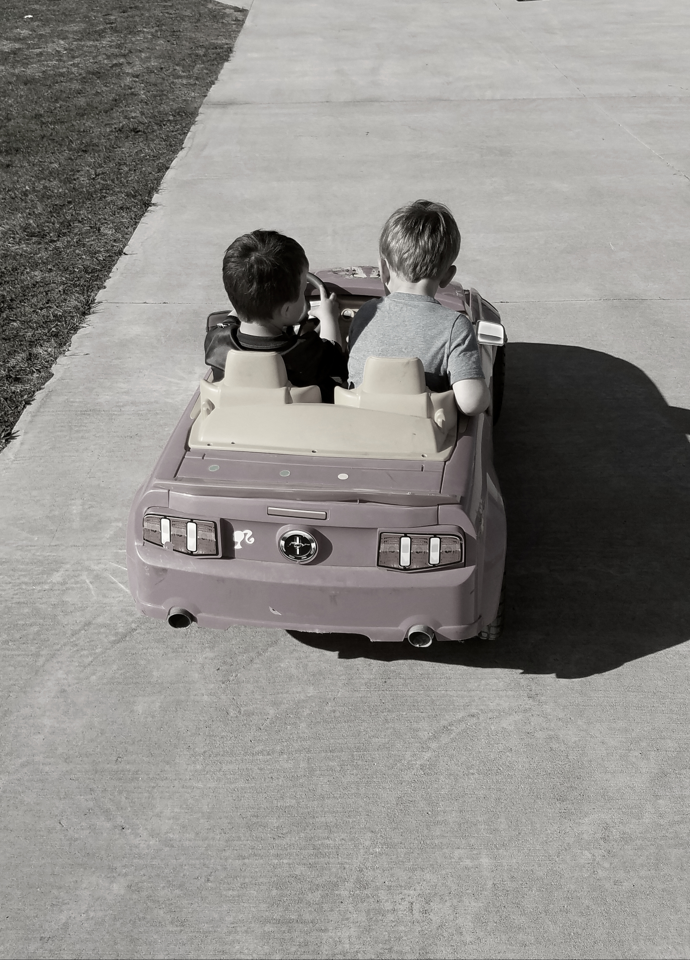 My son, the backseat driver, with his cousin behind the wheel.