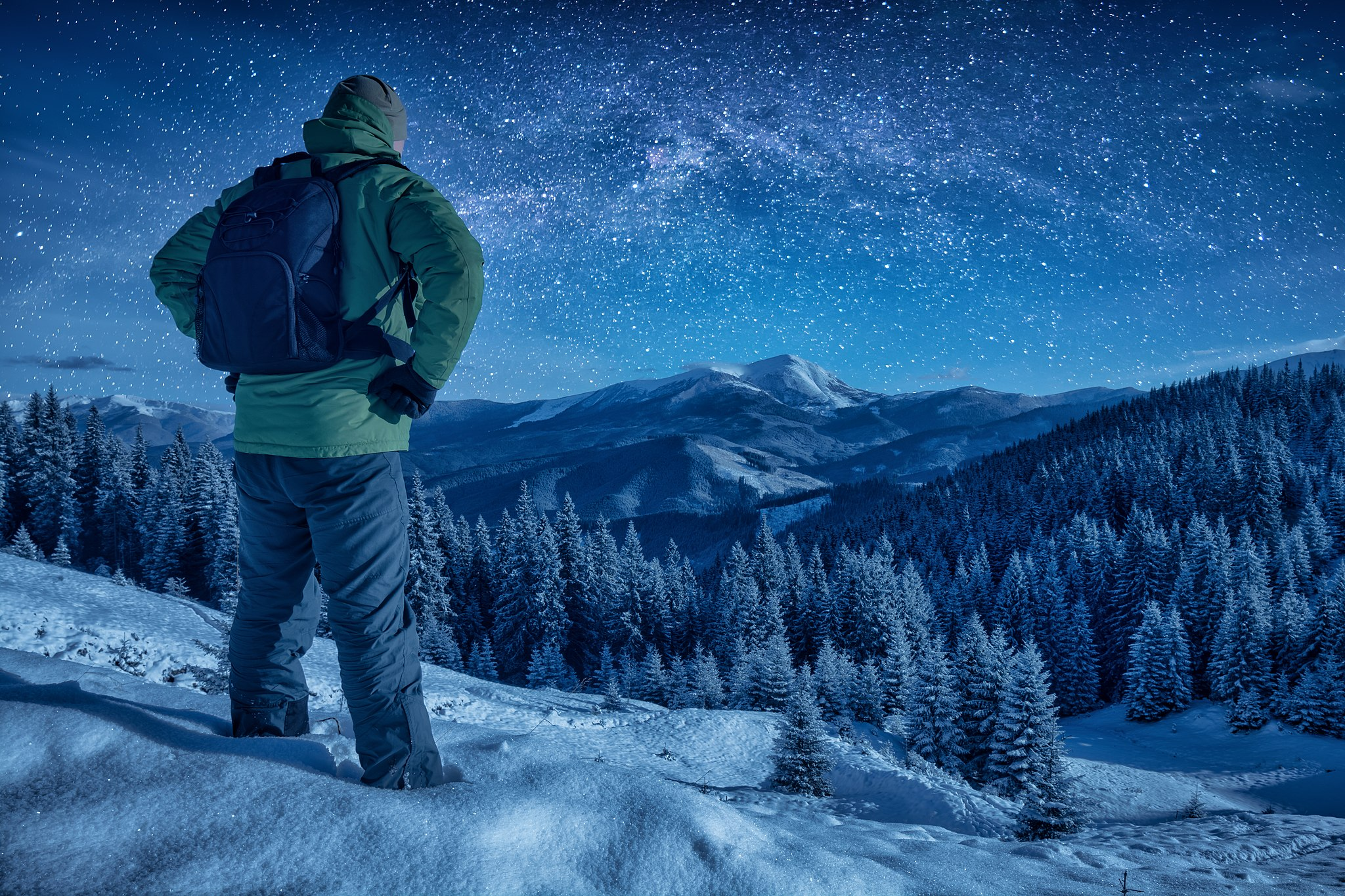 A climber standing on a snowy slope at night. Milky way in a starry sky above the mountain top; image by Vian via Wikimedia Commons.