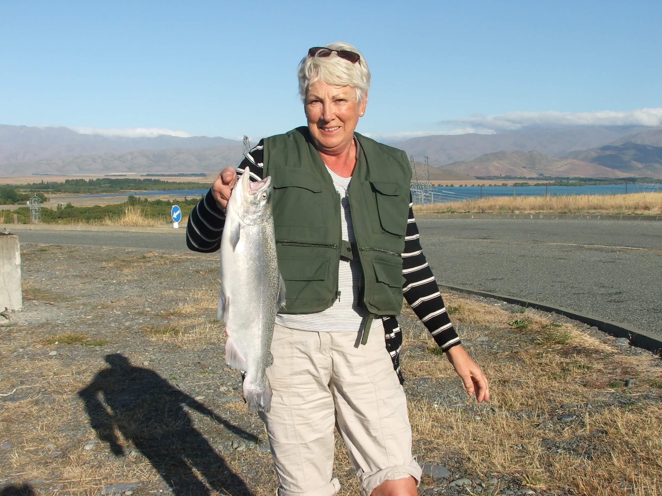 Pam with her salmon at Ohau C Lake Benmore in the background.JPG