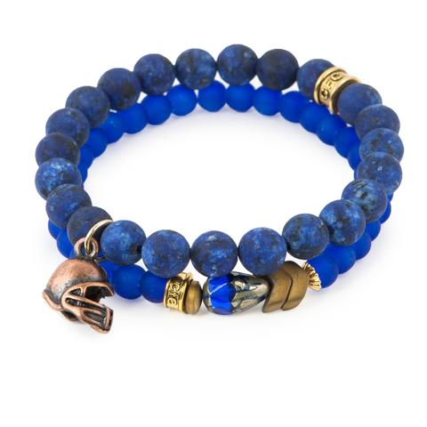 "Team Spirit  (Set of Two)   Blue dyed jade and glass bracelet set of two with Czech glass accent, antique bronze-tone hematite detail, and copper-tone helmet charm. Measures approximately 7.5"" in length. With the purchase of this bracelet set, 25% of gross profit goes to Water.org.  All bracelet sets come with a pouch and a hang-tag detailing the mission of each charity."