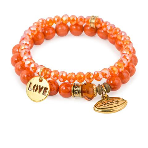 "Love Football  (Set of Two)   Orange fossil and crystal glass bracelet set of two with Czech glass accent, gold love, and football charms. Measures approximately 7.5"" in length. With the purchase of this bracelet set, 25% of gross profit goes to Best Friends Animal Society.  All bracelet sets come with a pouch and a hang-tag detailing the mission of each charity."