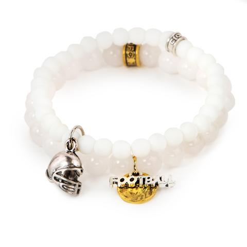 """Game On!  (Set of Two)   White dyed jade bracelet set of two with mixed metal football charms. Measures approximately 7.5"""" in length.With the purchase of this bracelet, 25% of gross profit goes to the Matthew Shepard Foundation.  All bracelet sets come with a pouch and a hang-tag detailing the charity's mission."""