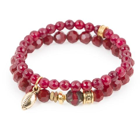 """1st Down (Set of Two)  Red-dyed jade and crystal glass bracelet set of two with Czech glass accent and gold mini football charm. Measures approximately 7.5"""" in length. With the purchase of this bracelet set, 25% of gross profit goes to V-Day.    Each bracelet comes with a hang-tag detailing the mission of each charity."""
