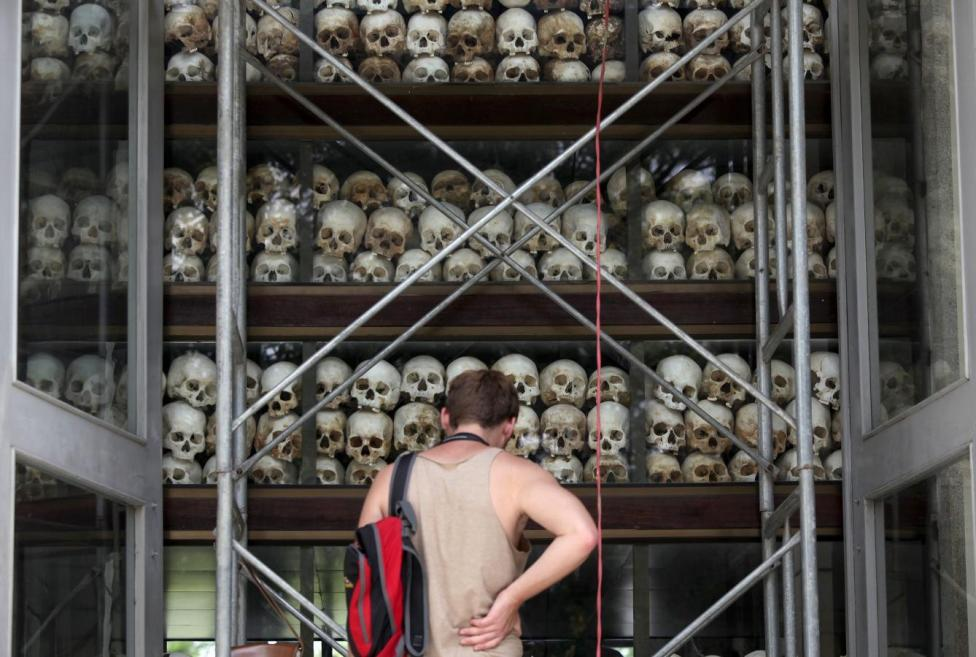 "A tourist visits a memorial stupa made with the skulls of more than 8,000 victims of the Khmer Rouge regime at Choeung Ek, a ""Killing Fields"" site located on the outskirts of Phnom Penh. August 4, 2014. Photo: REUTERS/Samrang Pring"