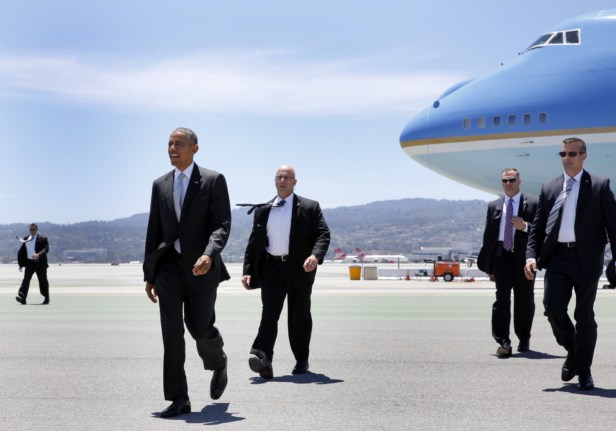 President Barack Obama and his Secret Service detail walk from Air Force One after landing at San Francisco International Airport on Friday, June 19, 2015.