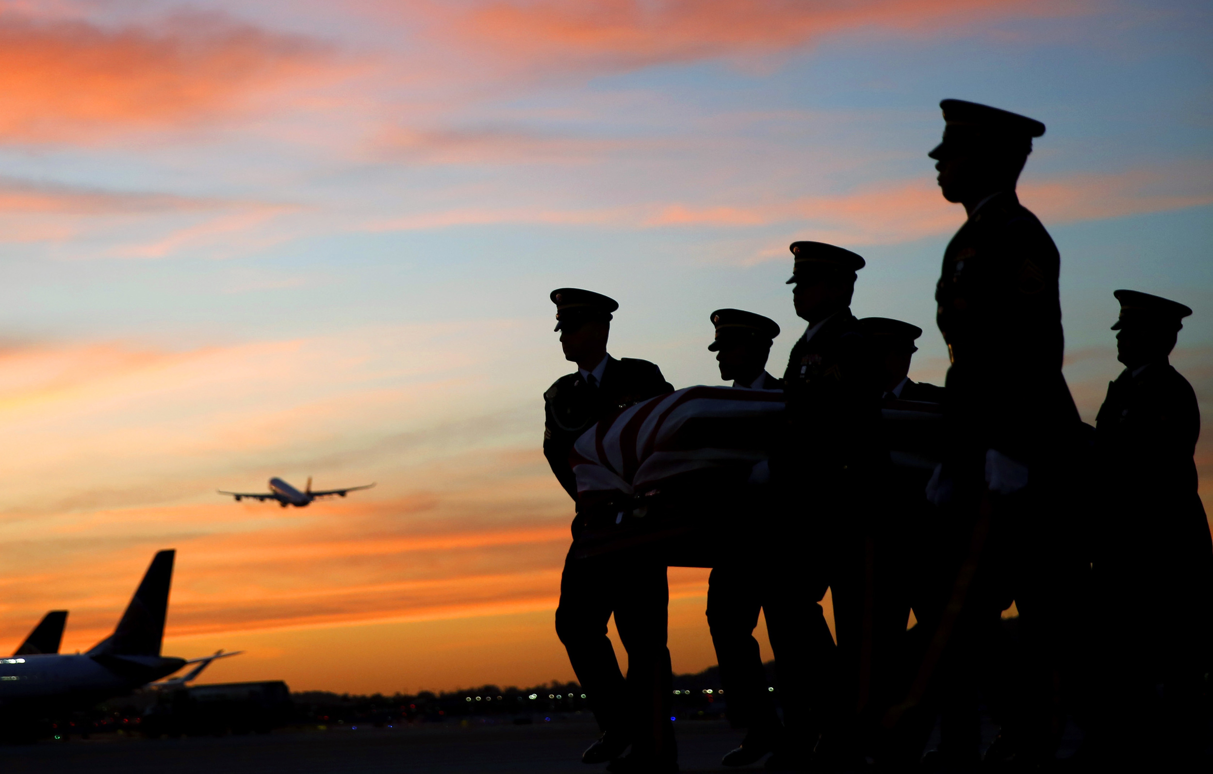 Six servicemen carry the remains of Army Cpl. Robert Graham from a plane at San Francisco International Airport on Wednesday, April 6, 2016.