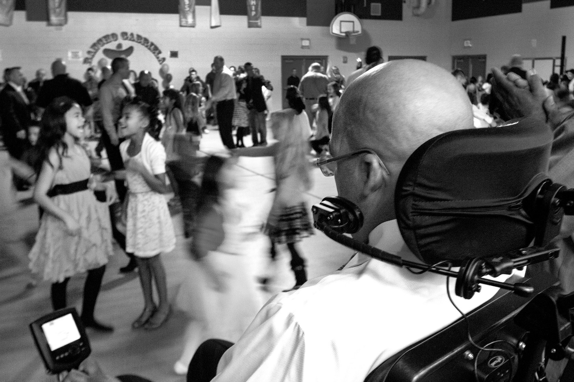 Mike watches his daughter Miah (left) laugh with her friend during a father-daughter dance in her school's gymnasium.