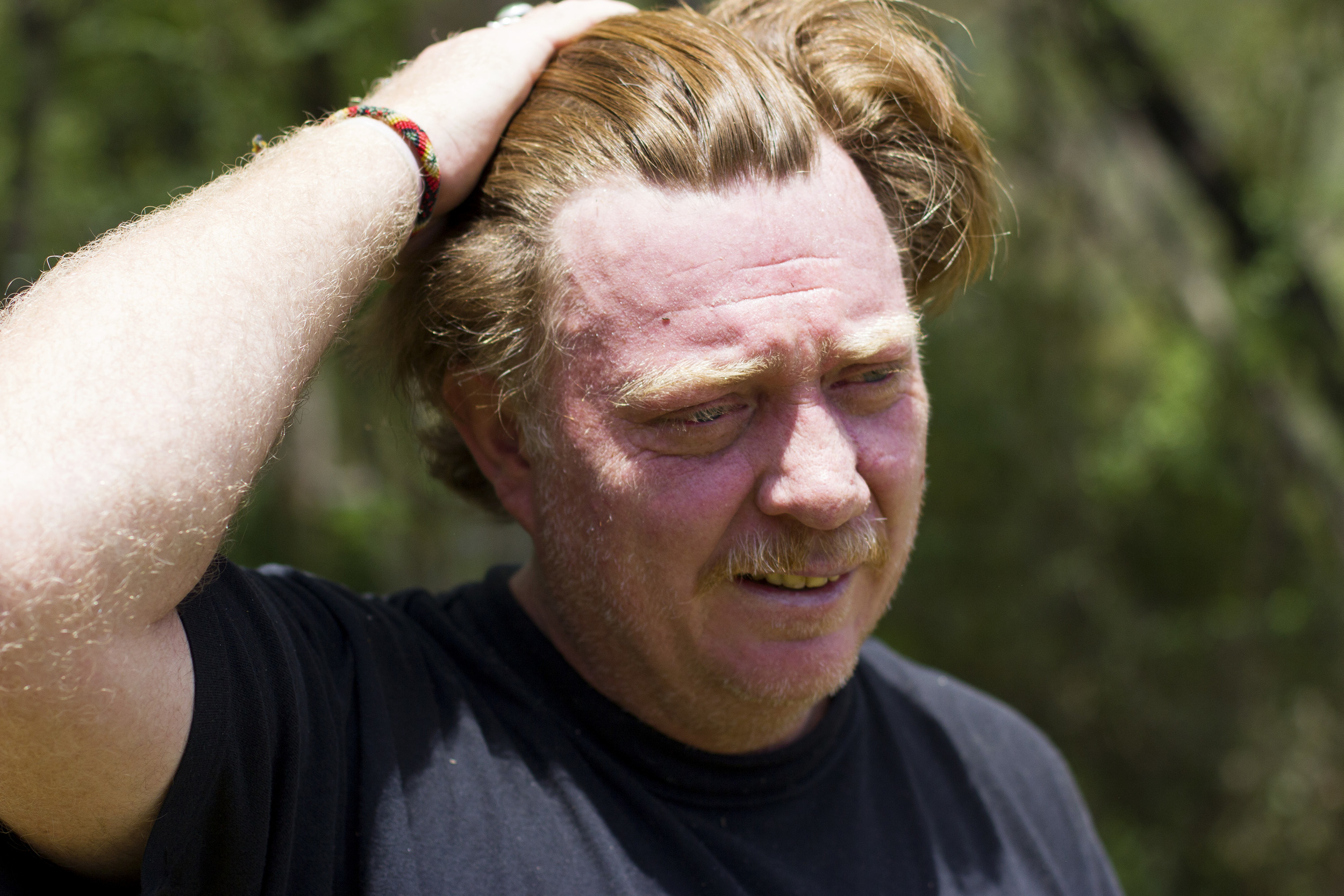 Virgil Edwards pushes his hair back after working for several hours in the heat and humidity of Chiapas, Mexico.Almost every day he prunes up to 10 trees, and he has a goal of planting 1,500 trees to make up for the ones he lost.