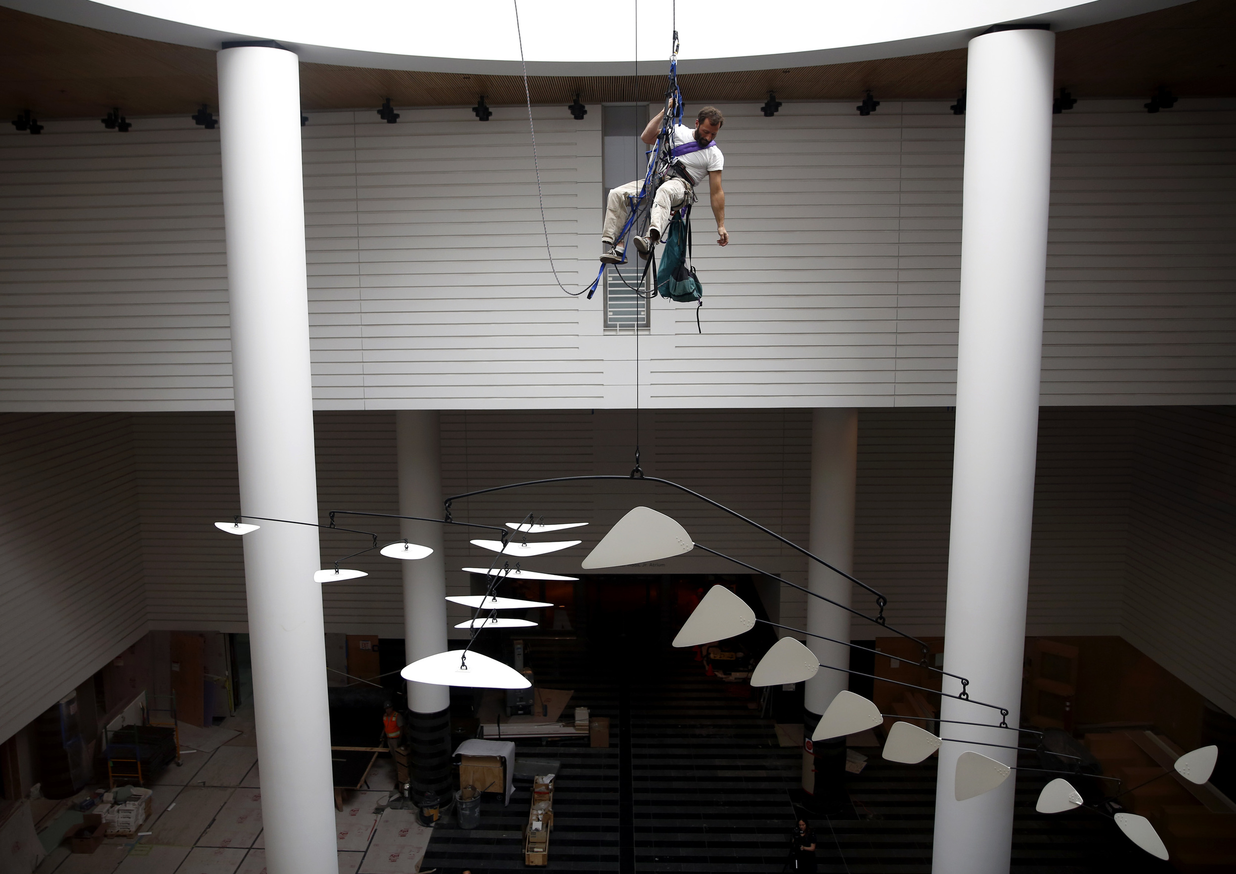 Lawrence LaBianca repels above a new Alexander Calder mobile at the Museum of Modern Art in San Francisco, California, on Tuesday, April 5, 2016.