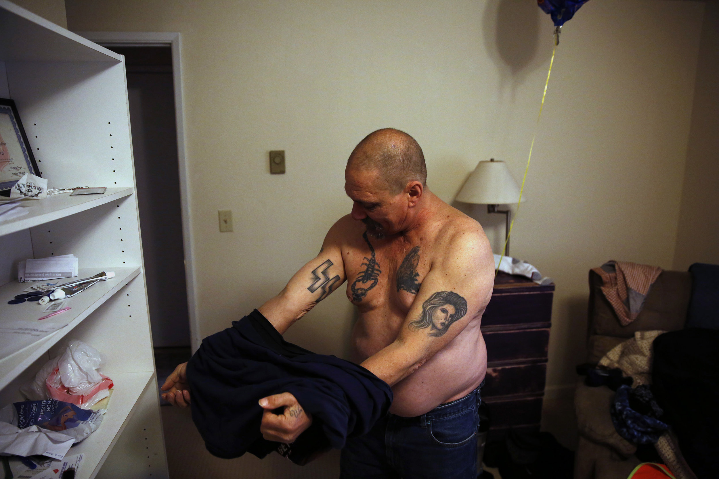 Dean shows off his tattoos — including Nazi SS bolts from his time in a California biker gang — while in his new apartment in Salem, Oregon, on Friday, Dec. 7, 2018.