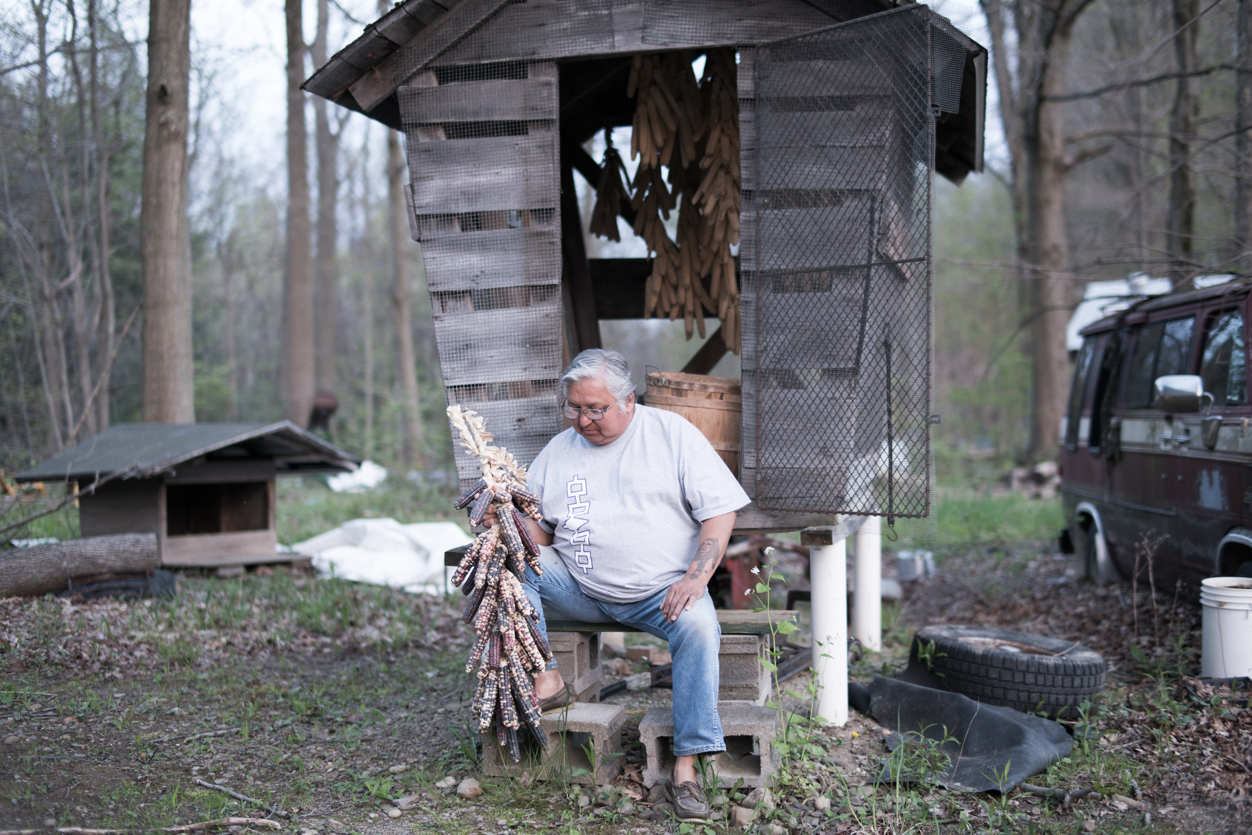 Rich Kettle, Seneca, in front of his corn crib with his braid of Hehgowa corn, gifted to him by friend from Onondaga. Rich was going to give up on planting this year until, as he says, he saw this braid of corn which called his name to plant.  The corn in the corn crib is white corn— the predominant variety of corn grown in the Haudenosaunee Nation. Corn cribs are the traditional way of storing seeds, keeping seeds alive is an important part of sovereignty. The quality of seed is important, everyone has always selected the best of their seed corn to make braids to plant the next season. Oftentimes corn is stored in individual corn cribs akin to this one. Now, however, as fewer people are maintaining seed tradition, Nations such as neighboring Onondaga realize the importance of ensuring seed sovereignty, and are currently constructing a tribal seed crib to maintain the corn of the community.   (Photo credit: Mateo Hinojosa)
