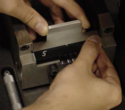 Figure 4 - This shows the Charpy Specimen Centering Gage. Notice how the silver notch of the tool enters the notch cutout in the black plastic specimen.