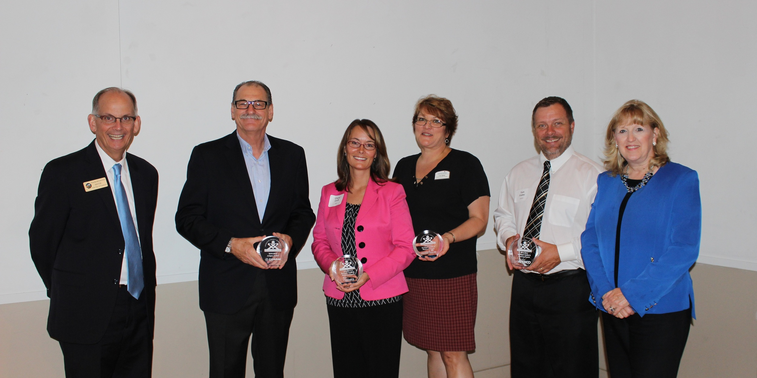2016 Health and Wellness and Judges Choice Photo  (from left to right): City of Frederick Mayor Randy McClement; Judges Choice Winner Michel Cyr, Canam Steel Corp; Spotlight Health & Wellness Winner Cheryl Cioffi, Sr. Vice President Patient Care Services, Frederick Memorial Hospital; Spotlight Health & Wellness Winner Carol Ditman, Executive Director, Country Meadows Retirement Communities; Spotlight Health & Wellness Winner Tom Fraley, Vice President of Support Operations, Avemco Insurance; Frederick County Executive Jan H. Gardner