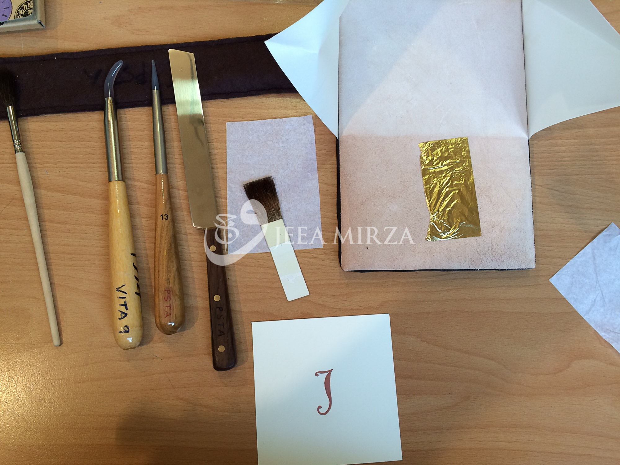 """© 2016 Wajeea Mirza.  The tools needed for raised gilding on gesso.     From left to right: 1) Squirrel hair gilder's mop 2) dog tooth burnisher 3) needle point burnisher 4) gilder's knife 5) small gilder's tip resting on glassine paper 6) gilder's cushion with a piece of loose gold leaf  7) a raised letter """"J"""" ready to be gilded"""