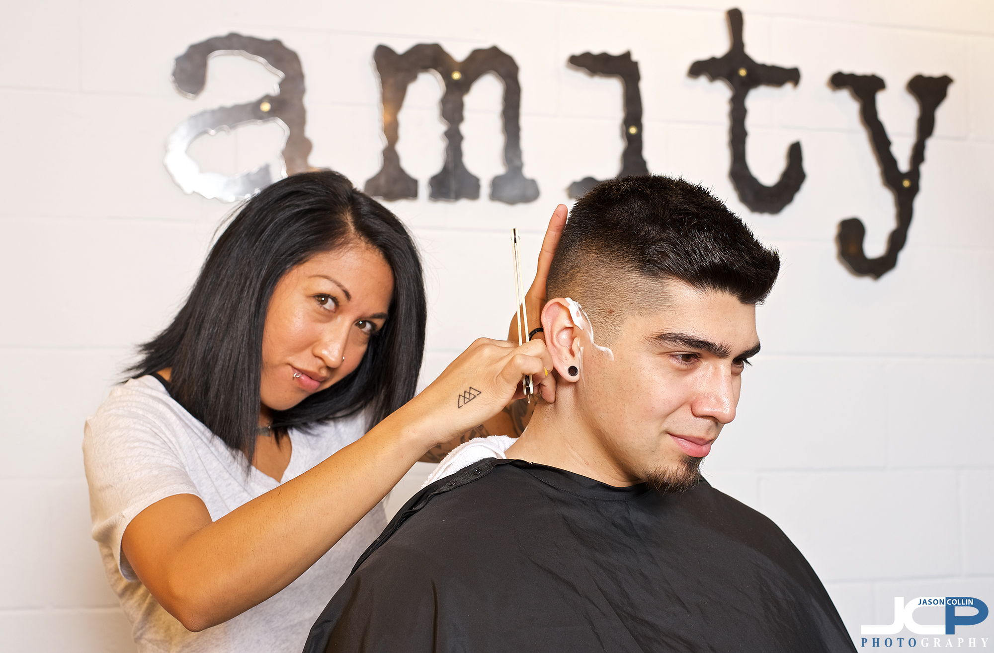 Felicia of Amity. A Hair Place gives a customer a shave at her hair salon in the Nob Hill area of Albuquerque, New Mexico