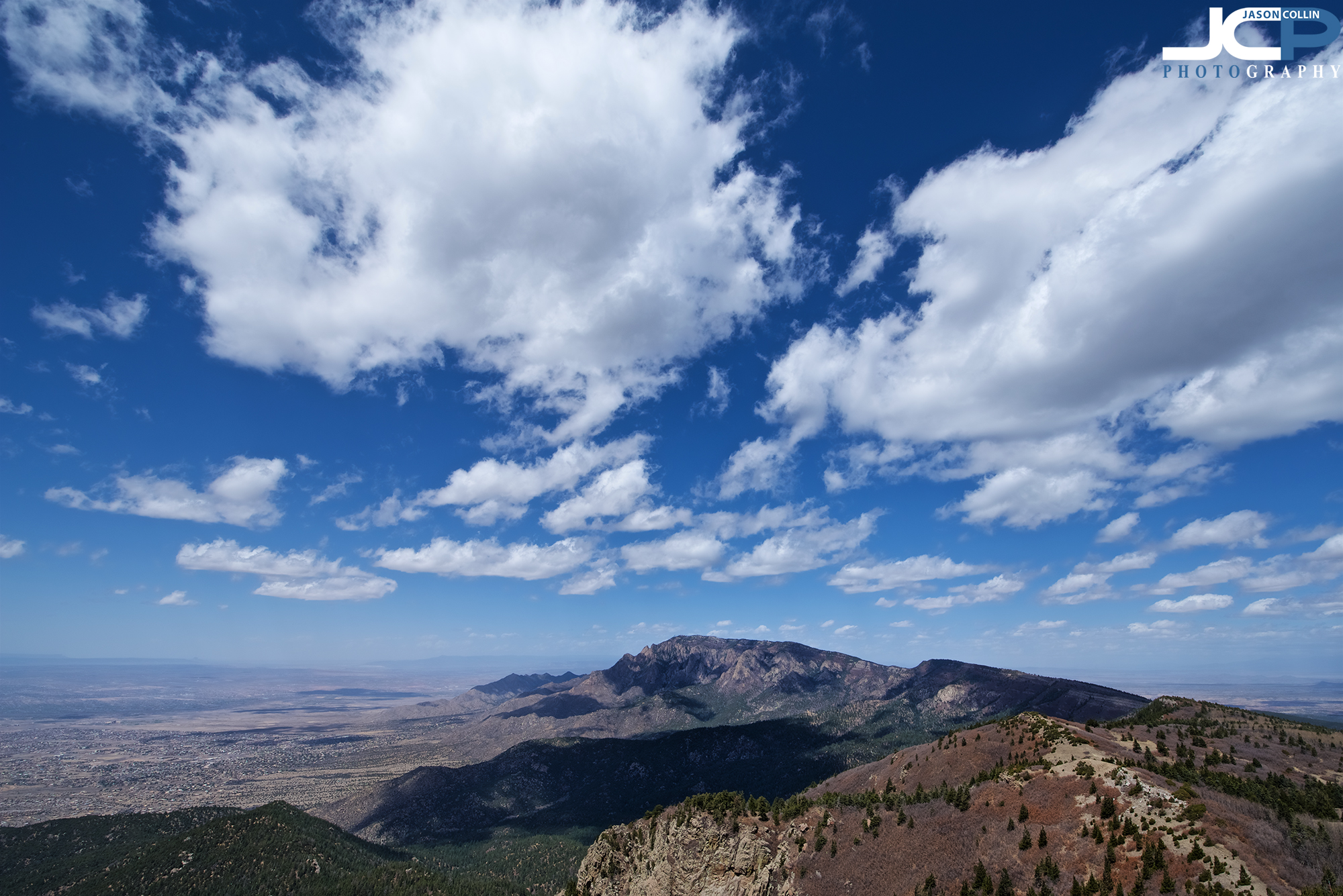 Looking at North Sandia Peak from the summit of South Sandia Peak with panorama view of Albuquerque, New Mexico