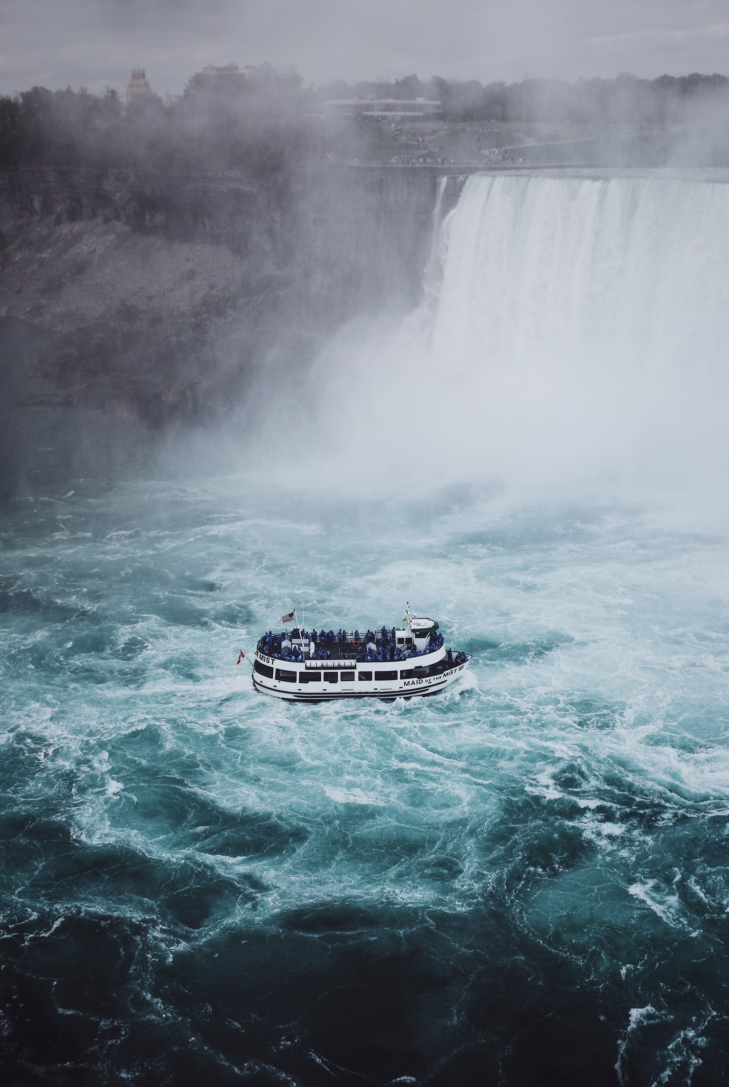 """People always ask me if I lived """"right in the Falls"""". Yes. Yes I did. Like this... If you look close enough, you can see me in a towel after I showered from the mist, brushing my teeth all the while tourists invade my home in plastic ponchos.  Photo by Renan Kamikoga on Unsplash"""