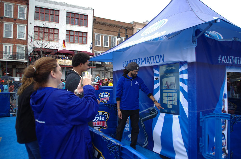 group gathered around Allstate Fansformation augmented reality photo booth