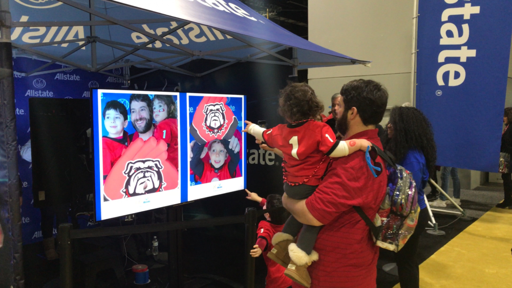 Man holding child in front of Allstate AR Photo Booth experience displays