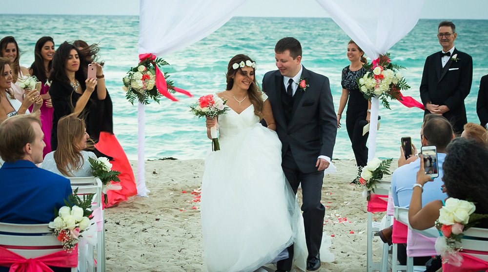 bride-groom-beach-wedding-ceremony-walking-aisle-happy-smiles-white-arch-flowers-pink-green-ribbons-chairs-sandy.jpg