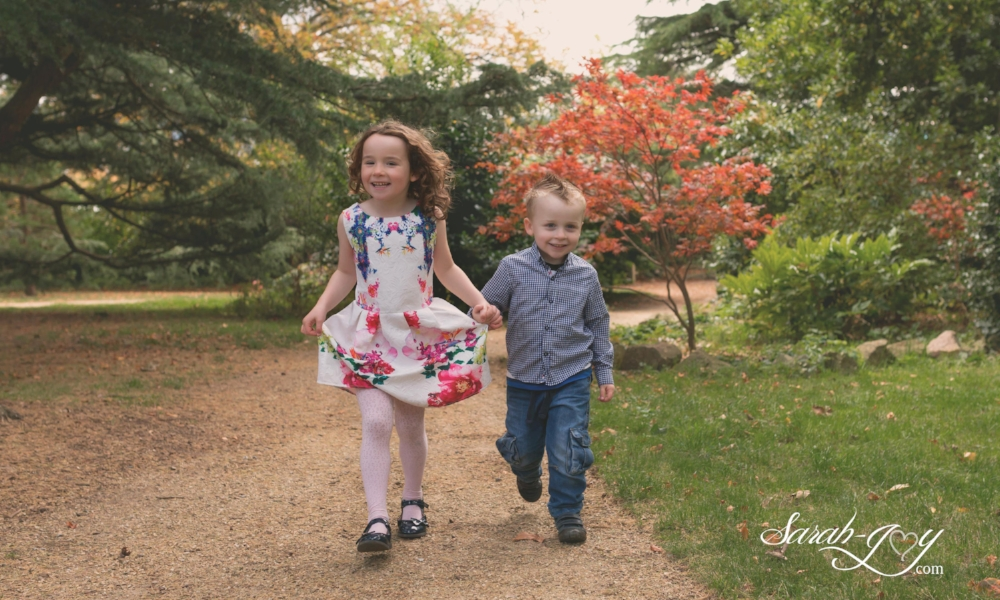 siblings holding hands and walking in the park