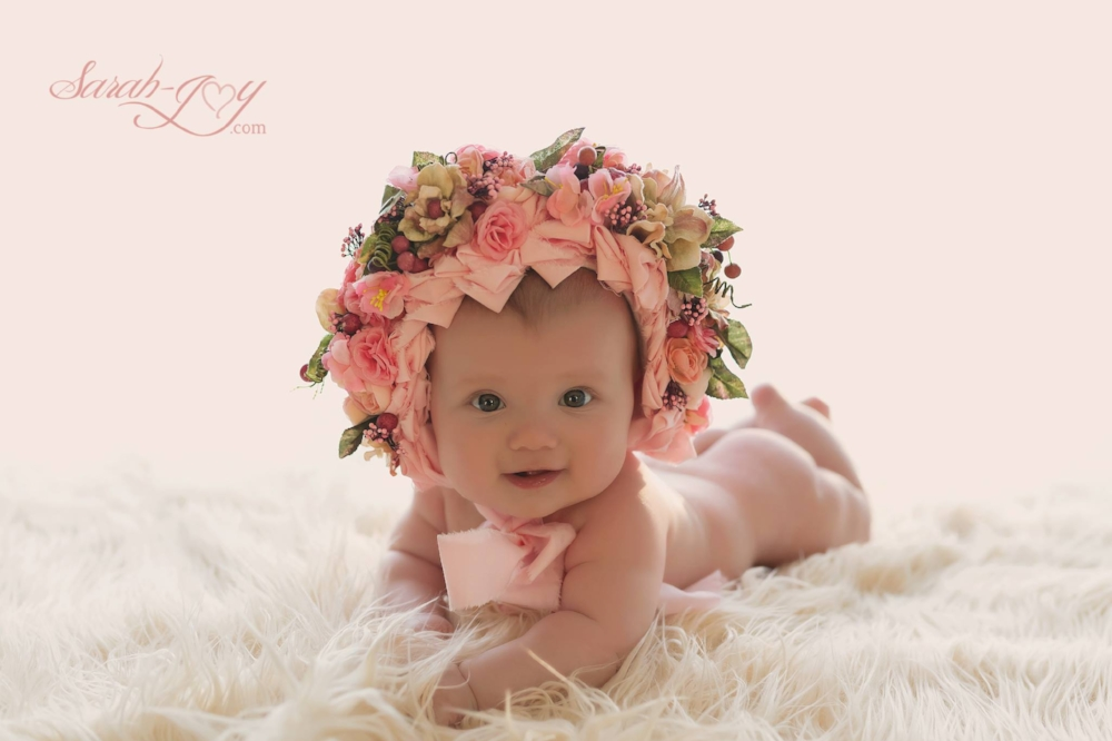 A baby on its tummy with a bonnet