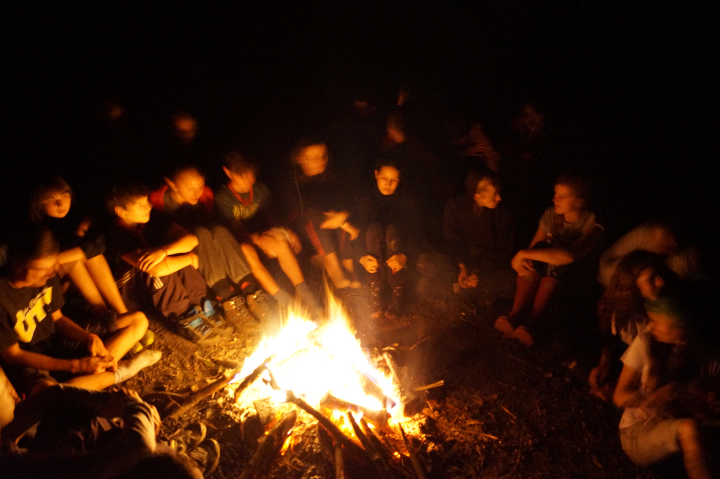 Sacred Earth young people gathered round a fire