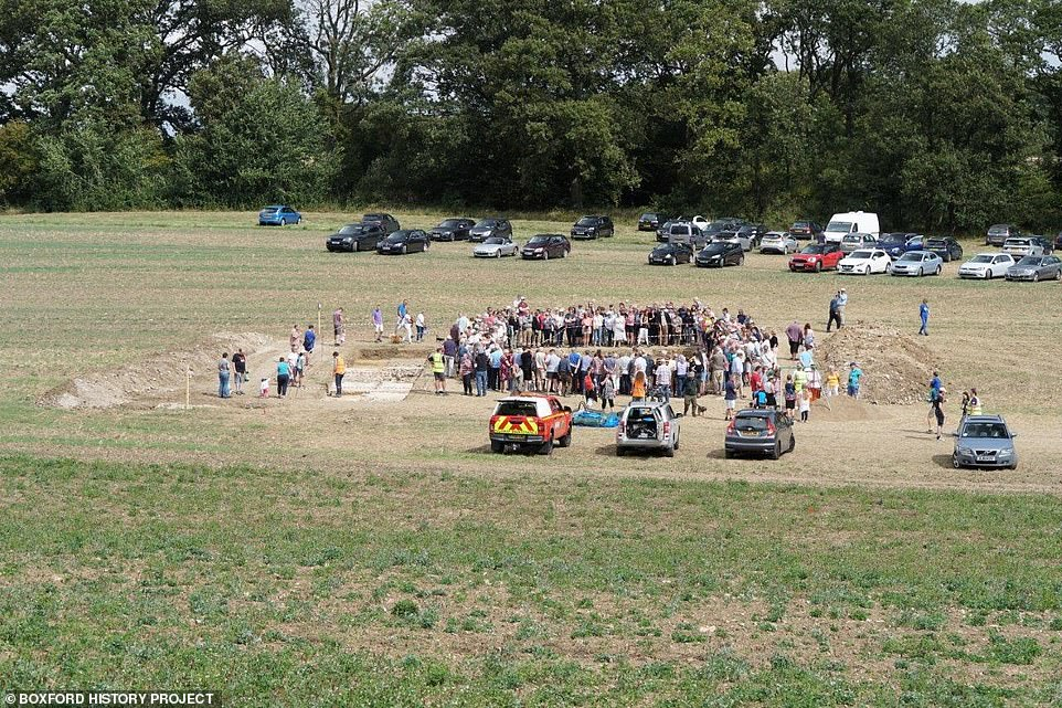 The public gathers around the square plot in the middle of the field. The prospect of removing the mosaic and putting it in a museum has been ruled out