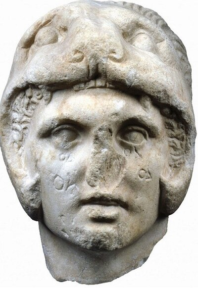 Marble head of Alexander the Great, found in the Kerameikos,    Athens c. 300 BC.    Head of Alexander the Great, made of pentelic marble. It was found in the Kerameikos, Athens. Alexander wears the lion's pelt, a common iconographic feature in depictions of the young king on coins, which hints at his descent from the mythical hero Herakles. The letters on Alexander's face were carved at a later period.