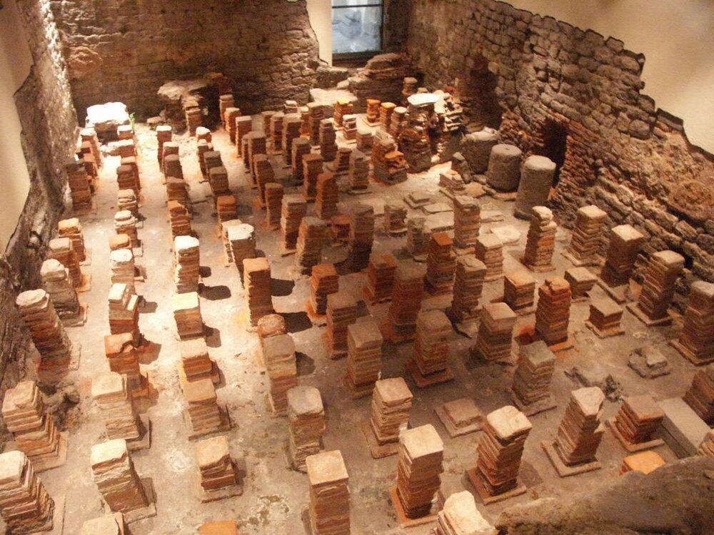 Caldarium από τα ρωμαϊκά λουτρά στο Bath, στη Βρετανία. Το δάπεδο έχει αφαιρεθεί για να αποκαλυφθούν οι άδειοι χώροι μέσω των οποίων θα ρέει ζεστός αέρας.