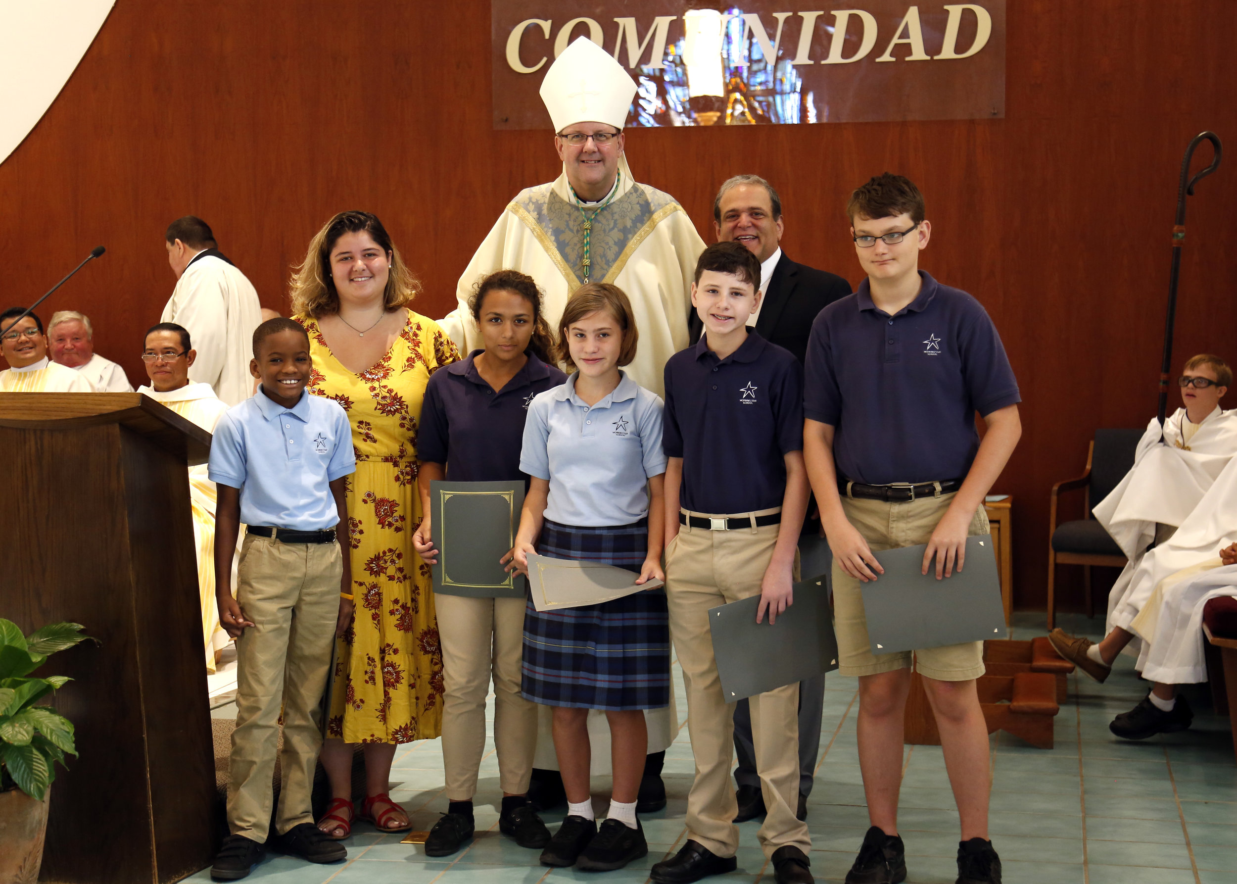 Scholarship winners (Front Left to Right) Jacob Green, Hailey Serafin, Gianna Lujan, Anthony Cano, and Samuel DeWitt with (Back Left to Right) Director of Gina Marie Rey Foundation Isabelle Galantino, Bishop Gregory Parkes, and President of Gina Marie Rey Foundation Peter Galantino.